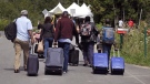 A family from Haiti approach a tent in Saint-Bernard-de-Lacolle, Quebec, stationed by Royal Canadian Mounted Police, as they haul their luggage down Roxham Road in Champlain, N.Y., Monday, Aug. 7, 2017. Quebecers living by the Canada-United States border where thousands of migrants have crossed irregularly into the country since 2017 will be eligible for payments of up to $25,000, the federal government announced Wednesday. THE CANADIAN PRESS/AP-Charles Krupa