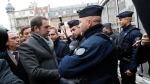 French Interior Minister Christophe Castaner, left, meets police officers as the Christmas market reopens in Strasbourg, eastern France, Friday, Dec.14, 2018. (AP Photo/Christophe Ena)