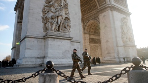 Soldiers patrol by the Arc de Triomphe in Paris, Friday, Dec.14, 2018. Anticipating a fifth straight weekend of violent protests, Paris' police chief said Friday that armored vehicles and thousands of officers will be deployed again in the French capital this weekend. (AP Photo/Francois Mori)