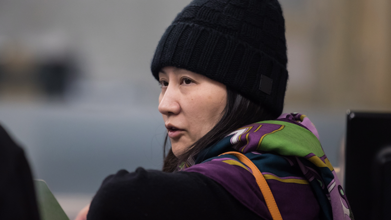 Huawei chief financial officer Meng Wanzhou, talks with a member of her private security detail after they went into the wrong building while arriving at a parole office, in Vancouver, on Wednesday, Dec. 12, 2018. THE CANADIAN PRESS/Darryl Dyck