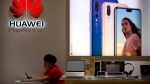 A sales clerk looks at his smartphone in a Huawei store at a shopping mall in Beijing Wednesday, July 4, 2018. (THE CANADIAN PRESS/AP-Mark Schiefelbein)
