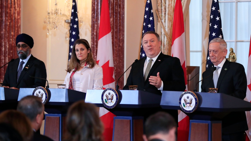 U.S. Secretary of State Mike Pompeo, second from right, with U.S. Defense Secretary Jim Mattis, right, and Canadian counterparts Minister of Foreign Affairs Chrystia Freeland and Minister of Defense Harjit Sajjan, left, speaks to reporters during a news conference following meeting at the State Department in Washington, Friday, Dec. 14, 2018. (AP Photo/Manuel Balce Ceneta)