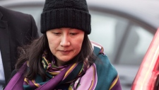 Huawei chief financial officer Meng Wanzhou, right, is escorted by a member of her private security detail while arriving at a parole office, in Vancouver, on Wednesday December 12, 2018. THE CANADIAN PRESS/Darryl Dyck