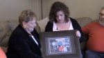 Darlene Nichol (right) hold a family picture that includes her sister, who was murdered 17 years ago. (CTV News)