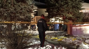 A member of the Calgary Police Service surveys the damage to a West Hillhurst home following a Friday night fire. A woman removed from the home did not survive..