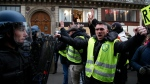 Demonstrators face riot police officers during a protest near the Opera house, Saturday, Dec. 15, 2018 in Paris. (AP Photo/Michel Euler)