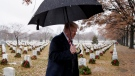 U.S. President Donald Trump walks with an umbrella from Section 60 of Arlington National Cemetery in Arlington, Va., Saturday, Dec. 15, 2018, after visiting during Wreaths Across America Day. (AP Photo/Carolyn Kaster)
