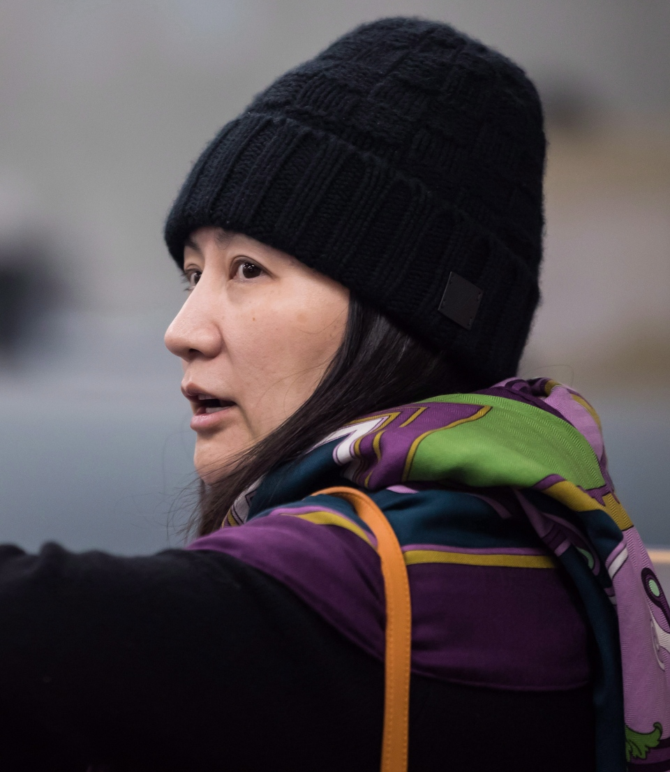 Huawei chief financial officer Meng Wanzhou, talks with a member of her private security detail after they went into the wrong building while arriving at a parole office, in Vancouver, on Wednesday December 12, 2018. (THE CANADIAN PRESS/Darryl Dyck)