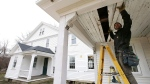 In this Thursday, Dec. 13, 2018 photo, carpenter Jeremy Parker works on a porch at the conclusion of a restoration of the home where Sarah Clayes lived in Framingham, Mass., after leaving Salem, Mass., following the 1692 witch trials. Clayes, who was jailed during the witch trials, was freed in 1693 when the hysteria died down. (AP Photo/Steven Senne)
