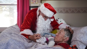 In this Saturday, Dec. 8, 2018 photo, Don West, 90, leans in to kiss his wife Jackie goodnight at Golden Days II Adult Foster Care in Charlotte following a Christmas party for residents and staff at the home. (Matthew Dae Smith/Lansing State Journal via AP)