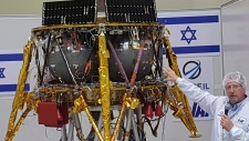 "Opher Doron, general manager of Israel Aerospace Industries' space division, speaks beside the SpaceIL lunar module, in a special ""clean room"" where the space craft is being developed, during a press tour of their facility near Tel Aviv, Israel, Tuesday, July 10, 2018.  (AP Photo/Ilan Ben Zion)"