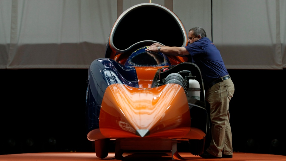 A technician places the cockpit cover on the British backed Bloodhound SSC streamliner car, Thursday, Sept. 24, 2015. (AP Photo/Alastair Grant)