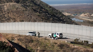 Honduran asylum seekers are taken into custody by U.S. Border Patrol agents after the group crossed the U.S. border wall into San Diego, California, seen from Tijuana, Mexico, Saturday, Dec. 15, 2018. (AP Photo/Moises Castillo)