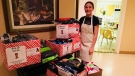 Lauren Martin shows off the 970 pairs of socks she delivered to the Inn out of the Cold program in St. Thomas, Ont. on Sunday, Dec. 16, 2018. (Brent Lale / CTV London)