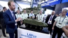 The Ontario-based company that is selling $15-billion worth of armoured vehicles to Saudi Arabia is warning the Liberal government that cancelling the deal will it cost billions of dollars in penalties. A General Dynamics LAV 6.0 is seen behind people as they gather around a scale model of a the same vehicle at the CANSEC trade show in Ottawa on Wednesday, May 30, 2018. (THE CANADIAN PRESS/Justin Tang)