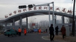 Residents pass by the entrance to the 'Hotan City apparel employment training base' where Hetian Taida has a factory, on Dec. 5, 2018. (Ng Han Guan / AP)