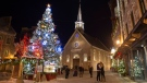 An unidentified couple, right, kiss in front of a giant Christmas tree on Place Royale and the Notre-Dame-des-Victoires church in the old historic area of Quebec City, Sunday, Dec. 16, 2018. THE CANADIAN PRESS/Jacques Boissinot