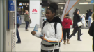 An STM representative hands out free smartphone straps at Berri-UQAM metro on Tuesday morning. The organization is hoping that the initiative will reduce the number of objects that fall onto the tracks each year. (CTV Montreal)