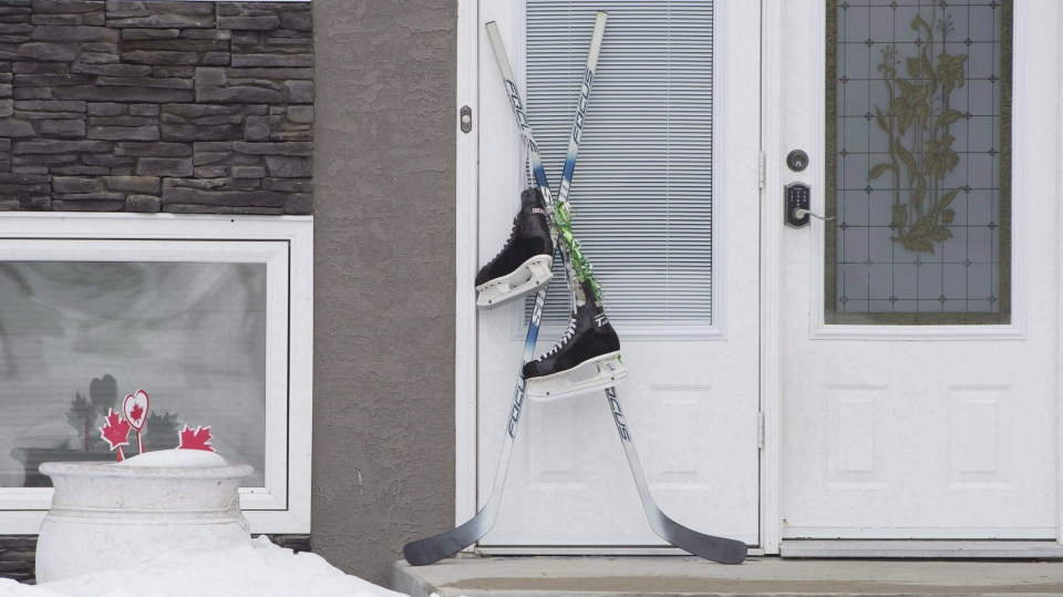 Hockey sticks and a pair of skates are seen outside the front door of a home in Montmartre, Sask., hometown of Humboldt Broncos' Adam Herold on Thursday, April, 12, 2018. THE CANADIAN PRESS/Jonathan Hayward