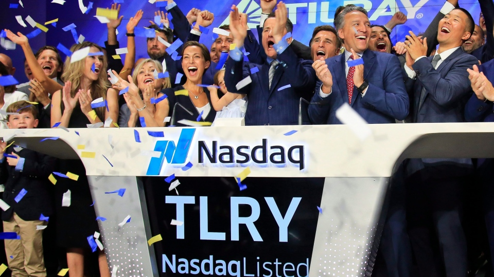 In this July 19, 2018, file photo Brendan Kennedy, third from right in front, CEO and founder of British Columbia-based Tilray Inc., a major Canadian marijuana grower, leads cheers as confetti falls to celebrate his company's IPO (TLRY) at Nasdaq in New York.(AP Photo/Bebeto Matthews, File)