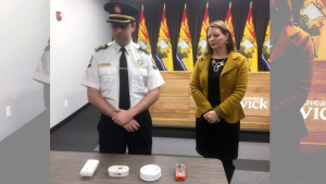 Michael Lewis, acting fire marshal for New Brunswick and Dr. Jennifer Russell, New Brunswick Chief medical officer of health, demonstrate carbon monoxide detectors in Fredericton on Thursday, Dec 20, 2018. THE CANADIAN PRESS/Kevin Bissett