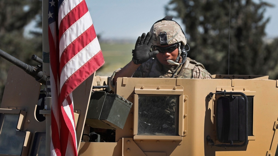 In this April 4, 2018 photo, a U.S. soldier waves as he sits on an armored vehicle, at a road leading to the tense front line with Turkish-backed fighters, in Manbij town, north Syria. (AP Photo/Hussein Malla)