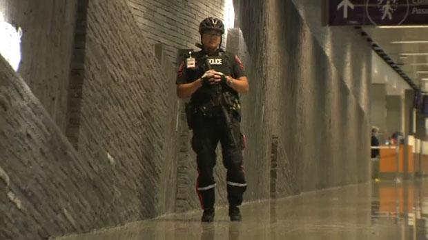 A Calgary police officer stands in a hallway at the Calgary airport following reports of an incident in the International Terminal.