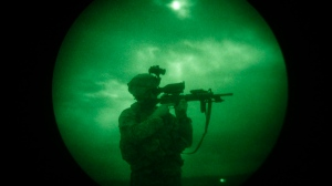 In this Monday, April 21, 2008 file photo, a U.S soldier looks through the scope of his weapon during a night patrol in Mandozai, in Khost province, Afghanistan, seen through night vision equipment. (AP Photo/Rafiq Maqbool)