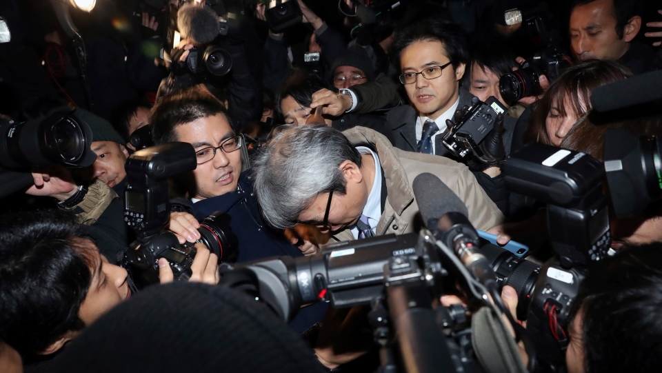Motonari Otsuru, center, defense lawyer of former Nissan chairman Carlos Ghosn, is surrounded by journalists as he leaves from Tokyo Detention Center where Ghosn and another former executive Greg Kelly are being detained, in Tokyo, Thursday, Dec. 20, 2018. (AP Photo/Eugene Hoshiko)