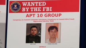 A poster displayed during a news conference at the Department of Justice in Washington, Thursday, Dec. 20, 2018, shows two Chinese citizens suspected to be with the group APT 10 carrying out an extensive hacking campaign to steal data from U.S. companies. (AP Photo/Manuel Balce Ceneta)
