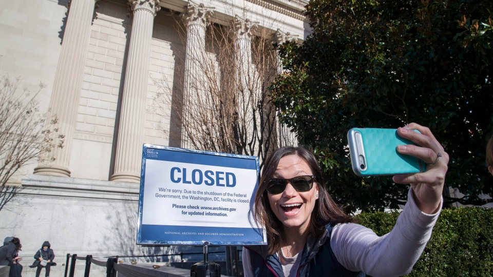 Jamie Parrish, from Minneapolis, takes a selfie in front of the closed sign at the National Archives, Saturday, Dec. 22, 2018 in Washington. (AP Photo/Alex Brandon)(AP Photo/Alex Brandon)