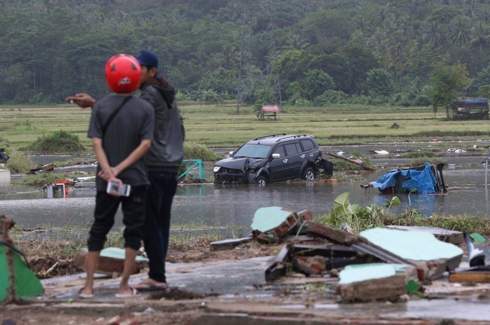Villagers stand near a car damaged by a tsunami in Carita, Indonesia, Sunday, Dec. 23, 2018. (AP Photo/Achmad Ibrahim)