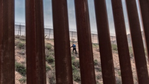A Honduran migrant w climbs an embankment after jumping over the U.S. border wall from Tijuana, Mexico, to San Diego, Calif., as seen from Tijuana, Mexico, Friday, Dec. 21, 2018.  (AP Photo/Daniel Ochoa de Olza)