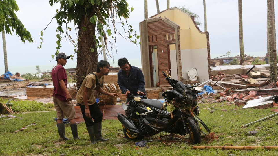 Residents inspect a motorcycle damaged by a tsunami at a cottage in Tanjung Lesung, Indonesia, Monday, Dec. 24, 2018. (AP Photo/Tatan Syuflana)