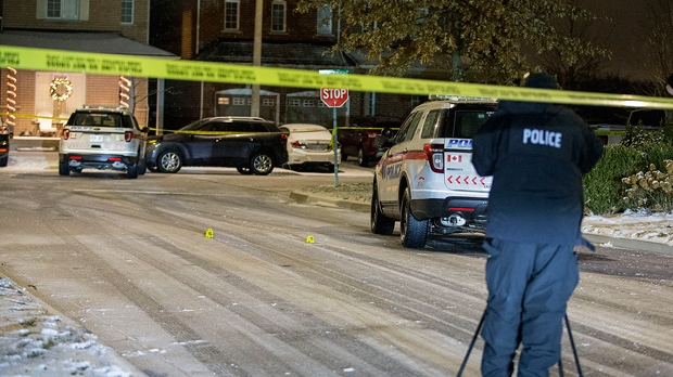 A police officer stands on a street in Richmond Hill where a 33-year-old man was shot dead on Dec. 24, 2018. (John Hanley)