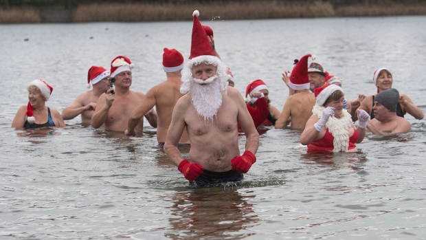 Members of the swimming club 'Berlin seals' wear Christmas costumes as they go for a swim in the Orankesee lake in Berlin, Tuesday, Dec. 25, 2018. (Paul Zinken/dpa via AP)