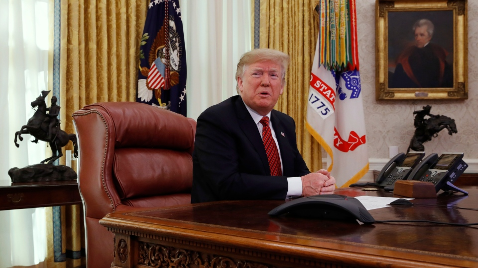 U.S. President Donald Trump answers questions from the media after speaking with members of the military by video conference on Christmas Day, Tuesday, Dec. 25, 2018, in the Oval Office of the White House. (AP Photo/Jacquelyn Martin)