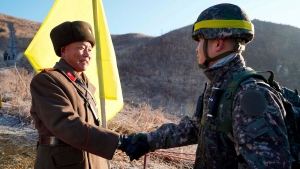 In this photo provided by South Korea Defense Ministry, South Korean army Col. Yun Myung-shick, right, shakes hands with North Korean army Lt. Col. Ri Jong Su before crossing the Military Demarcation Line inside the Demilitarized Zone (DMZ) to inspect the dismantled North Korean guard post in the central section of the inter-Korean border in Cheorwon, Wednesday, Dec. 12, 2018. (South Korea Defense Ministry via AP)
