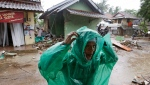 A man puts on a rain coat near debris at a tsunami-ravaged area in Carita, Indonesia, Wednesday, Dec. 26, 2018. (AP Photo/Achmad Ibrahim)