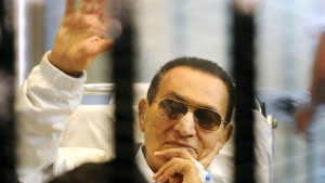 In this April 13, 2013 file photo, former Egyptian President Hosni Mubarak waves to his supporters from behind bars as he attends a hearing in his retrial on appeal, in Cairo, Egypt. (AP Photo, File)