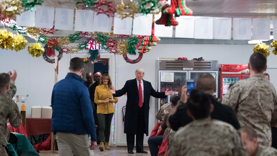 U.S. President Donald Trump and first lady Melania Trump arrive to visit with members of the military at a dining hall at Al Asad Air Base, Iraq, Wednesday, Dec. 26, 2018. (AP Photo/Andrew Harnik)