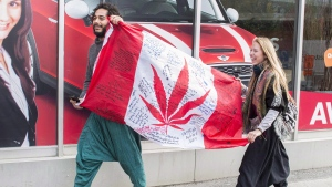 People hold up a Canadian flag with a marijuana logo on it outside a government cannabis store in Montreal, Wednesday, October 17, 2018. THE CANADIAN PRESS/Graham Hughes