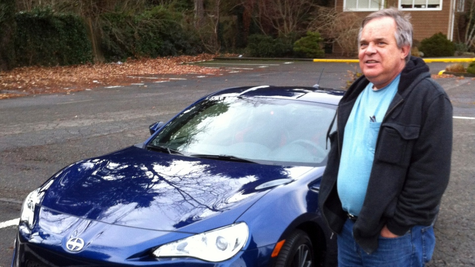 In this Dec. 14, 2013, photo provided by Shashi Karan, Alan Naiman poses with his new car, an unusual extravagance for him, in Seattle. (Shashi Karan via AP)
