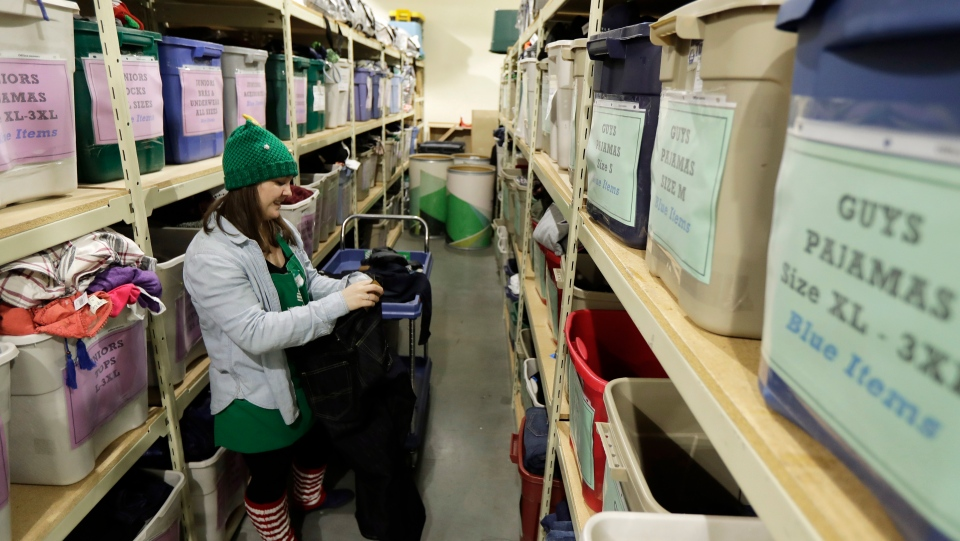 In this Friday, Dec. 21, 2018, photo, Maddi Heim folds and sorts donated clothes at Treehouse, a nonprofit organization in Seattle that serves the needs of children in the foster-care system. The charity was one of several that received donations from the $11 million secret estate of Alan Naiman -- a social worker who died from cancer earlier in 2018 after living a private life of frugality and concern for children facing hardship. (AP Photo/Ted S. Warren)