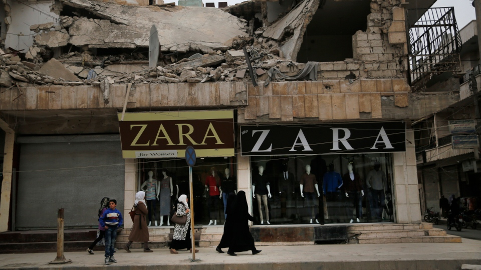 In this March 28, 2018 file photo, women walk in front of clothes shops, on a commercial street, in Manbij, north Syria. On Friday, Dec. 28, 2018, Syria's military announced it has taken control the flash-point Kurdish-held town of Manbij, where Turkey has threatened an offensive. The announcement Friday came shortly after the main Syrian Kurdish militia invited the government to seize control of Manbij to prevent an attack (AP Photo/Hussein Malla, File)