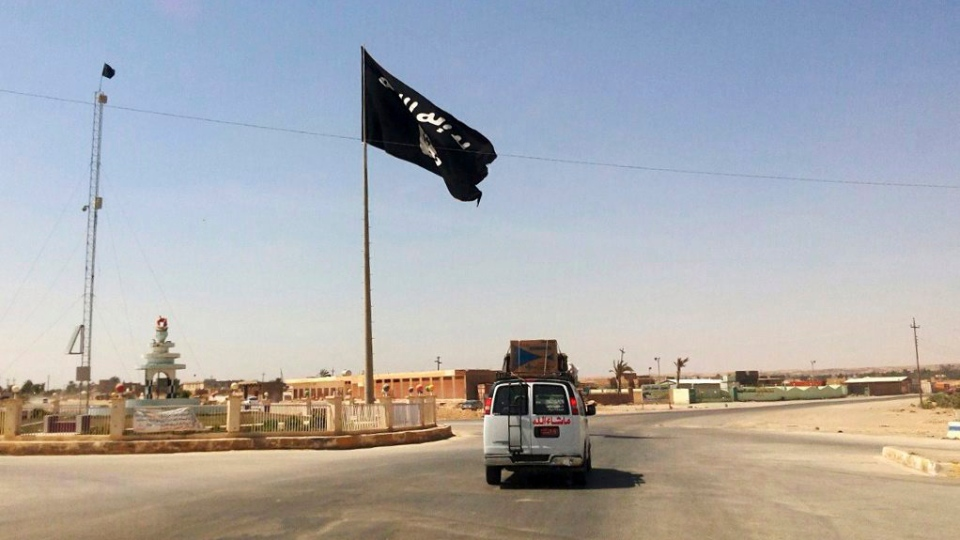 This Tuesday, July 22, 2014 file photo shows a motorist passing by a flag of the Islamic State group in central Rawah, 175 miles (281 kilometers) northwest of Baghdad, Iraq. (AP Photo)