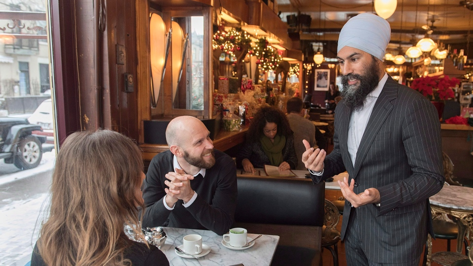 NDP Leader Jagmeet Singh speaks to a man and a woman in a coffee shop during a tour of the Montreal borough of Outremont, Saturday, December 22, 2018, ahead of federal byelection which is expected to be called in early 2019. (THE CANADIAN PRESS/Graham Hughes)