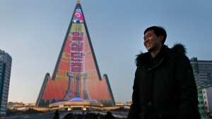 In this Dec. 20, 2018 photo, light designer Kim Yong Il smiles during an interview with the Associated Press as his creation, the light show displaying propaganda messages on the facade of the pyramid-shaped Ryugyong Hotel, is seen in the background in Pyongyang, North Korea. (AP Photo/Dita Alangkara)