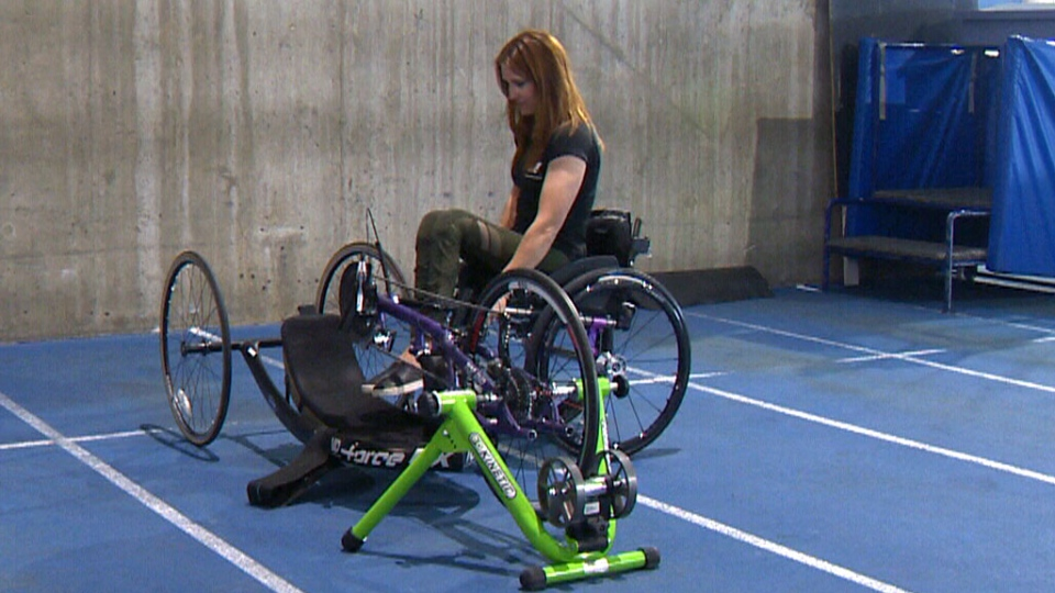 Paracyclist Kara Douville looks at her handcycle in Calgary. Douville hopes to represent Canada at the 2020 Paralympics in Tokyo.