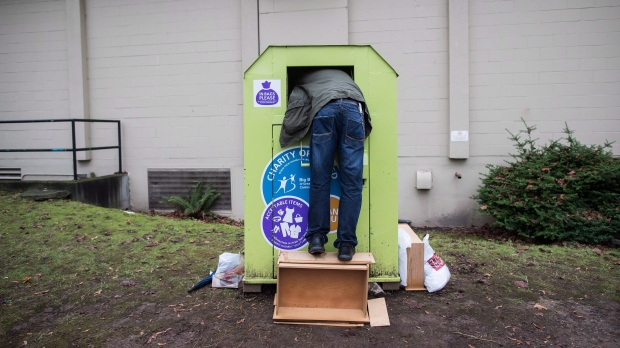 FILE -- A man tries to retrieve items from a clothing donation bin in Vancouver, on Wednesday, Dec. 12, 2018. (THE CANADIAN PRESS/Darryl Dyck)